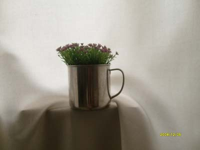 Old metal cup with tiny flowers.